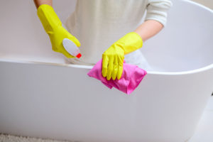 Woman cleaning a bathtub with gloves and cleaning solution